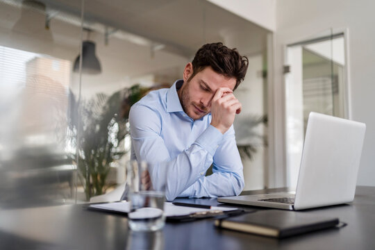 Tired businessman at desk in office