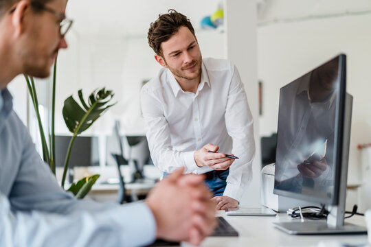 Male entrepreneur discussing over computer with colleague in office