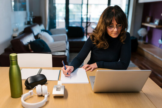 Mature woman writing in paper while sitting by laptop at home