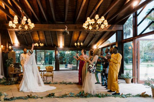 Bride throwing bouquet toward friends standing behind at banquet