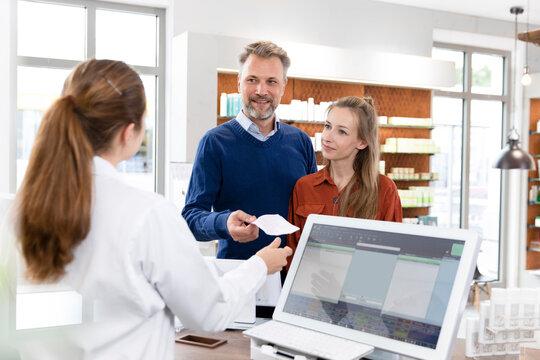 Male customer giving prescription list to female pharmacist at pharmacy checkout