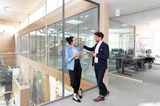 Male and female entrepreneurs discussing while standing near glass wall in factory