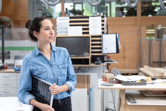 Thoughtful businesswoman holding solar panel model concept while looking away in factory