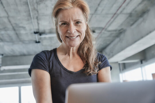 Smiling mature woman with laptop in loft apartment at home