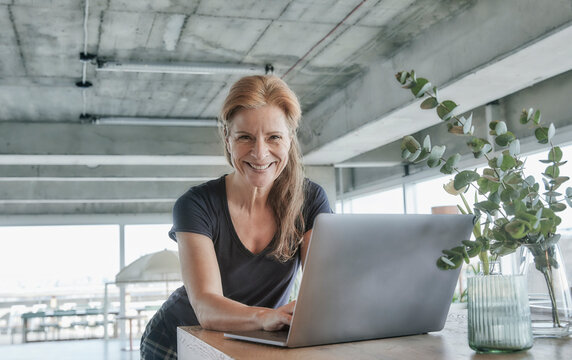Smiling mature woman using laptop at table in loft apartment at home