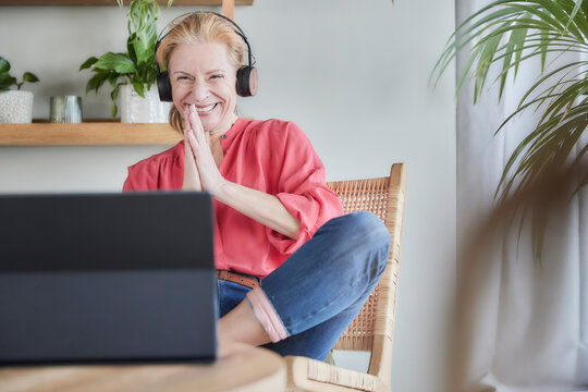Smiling woman greeting during video call on laptop at home