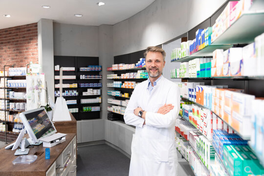Male pharmacist with arms crossed standing by shelf in store