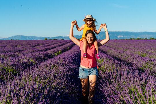 Portrait of mother piggybacking little daughter in vast summer lavender field