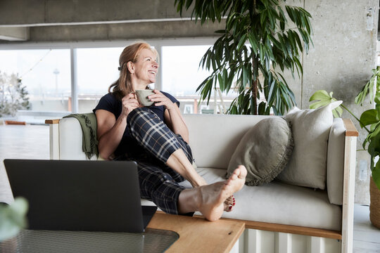 Smiling woman with laptop holding coffee cup while sitting on sofa at home