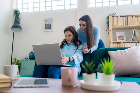 Mature businesswoman using laptop while daughter assisting at sofa in home office