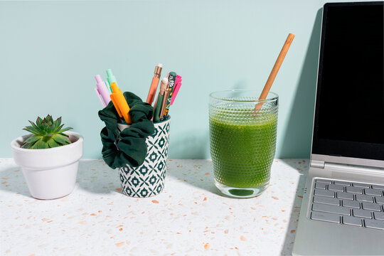 Succulent plant, laptop and healthy green juice over desk at home