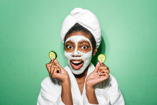 Young woman with facial mask holding cucumber while standing against green background
