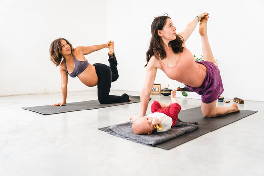 Two millennial women friends having fun together in gym on mat doing yoga exercises - Mother with baby practices with pregnant person Concept of physical and mental health during maternity Copy space