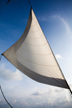 A white sail catching the winds on open ocean across the Caribbean Sea.