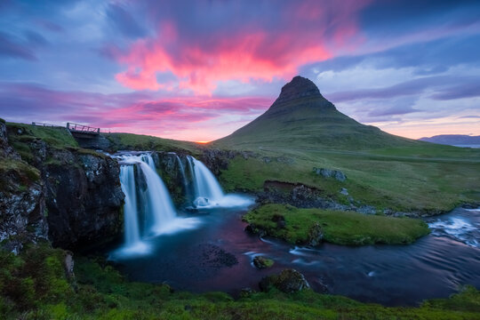 Colorful sunset over mountains and a waterfall in Iceland.