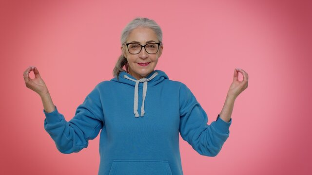 Keep calm down, relax, inner balance. Mature old granny woman breathes deeply with mudra gesture, eyes closed meditating with concentrated thoughts peaceful mind. Senior grandmother on pink background