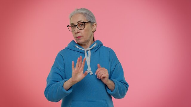 I am dont want it, not me. Confused elderly good-looking granny woman pointing fingers herself ask say who why me no thanks i do not need it. Senior old grandmother on pink background. People emotions