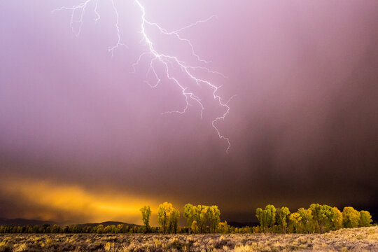 A lightning bolt strikes toward Jackson Hole, Wyoming during a storm.