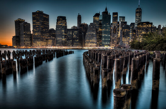 Twinkling lights of the skyscrapers in Lower Manhattan as twilight illuminates the pilings in the East River by Brooklyn Bridge Park, New York City