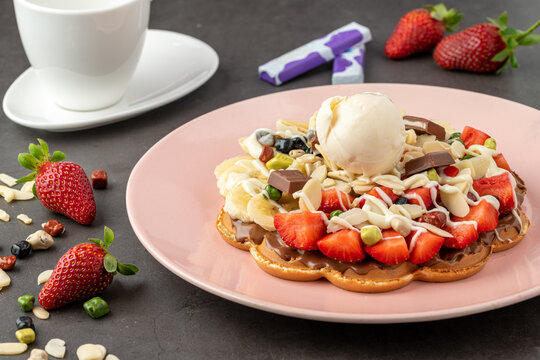 Heart waffle with banana and strawberry with gummy candy and ice cream on it.