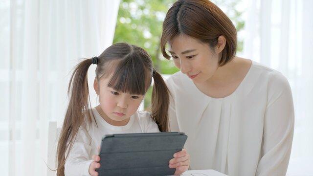 タブレットを使う女の子とお母さん