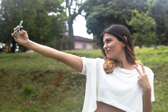 latina woman with taking selfie making peace sign