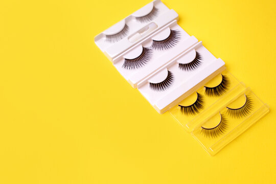 Set, collection of black false eyelashes on trendy bright yellow background, lashmaker concept, beautician industry, beauty salon flyer, coupon, minimal stylish card, copy space