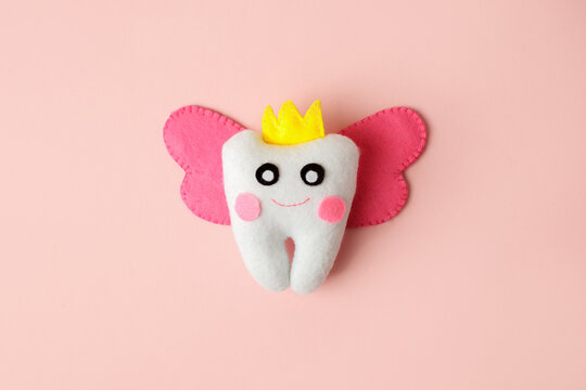 Cute toy for Tooth Fairy Day as funny smiling cartoon character of tooth fairy with crown, wings on pink background, copy space flyer, concept children milk toothless, funny toy, handmade felt diy