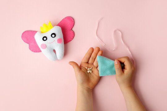 Felt tooth fairy pillow in kids hands on pink background with copy space for text. Handmade children's felt tooth fairy pillow. Stuffed toy crafts idea. Happy Tooth Fairy day card