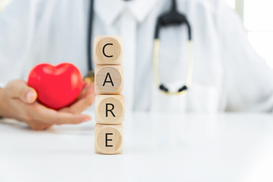 Medicare word written on cube shape wooden blocks. Doctor holding heart on his hand.