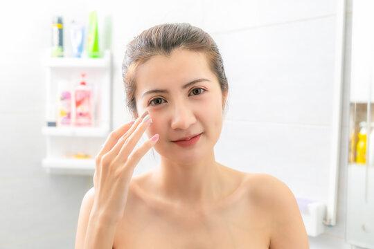 Asian Beauty Woman apply face cream in bathroom.