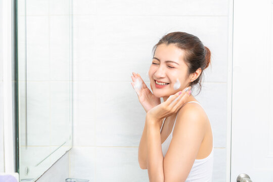 Young beauty woman washing her face in bathroom.