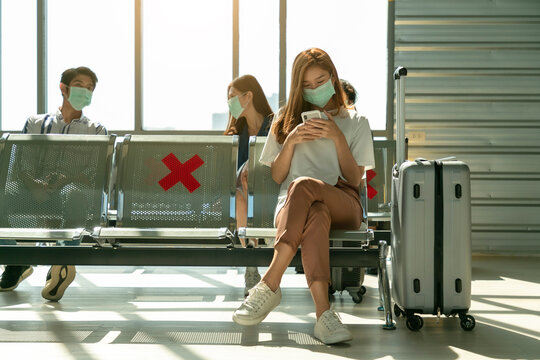 Young asian female passenger on smart phone and laptop sitting in terminal hall while waiting for her flight.