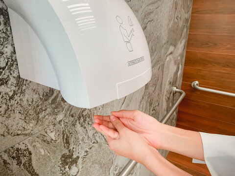 A man hands using automatic hand dryer in public toilet or restroom hygiene concept.