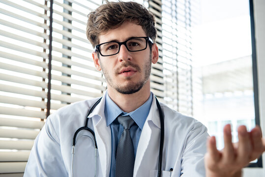 Young male doctor looking at camera explaining and talking with patient online via video calling, distance medical consulting service and telehealth concepts
