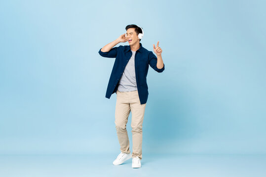 Smiling young handsome Asian man listening to streaming music on wireless headphones in isolated light blue studio background