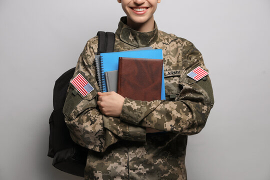 Female cadet with backpack and notebooks on light grey background, closeup. Military education