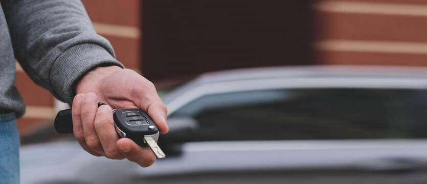 Man in front of the new car and holding keys. Salesman is carrying the car keys delivered to the customer at the showroom .  Rent, credit, insurance, car purchase. Copy space. Banner.