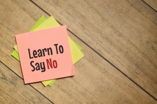 Learn To Say No wording with sticky note over a wooden background. Selective focus image