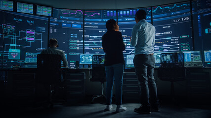 Fototapeta In the System Control Room Project Manager and IT Technical Engineer Have Discussion, they're surrounded by Multiple Monitors with Graphics. Big Monitor Shows Interactive Server Blockchain Info. obraz