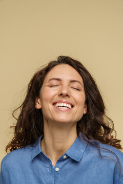 Closeup shot of happy overjoyed curly girl isolated on beige background laugh with open mouth, closed eyes. Extremely satisfied millennial female in casual jeans shirt cheering, excited, joyful face