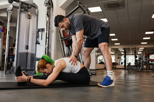 Male personal trainer assisting fit woman in stretching on mat in gym