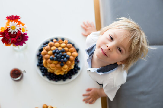 Sweet toddler child, boy, eating bubble waffles with fruits at home for breakfast