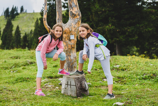 Children in frontWooden Signpost on Velika Planina in Slovenia.