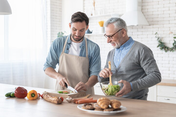 Senior elderly caucasian old father teaching his son how to cook dinner, lunch, prepare food and...