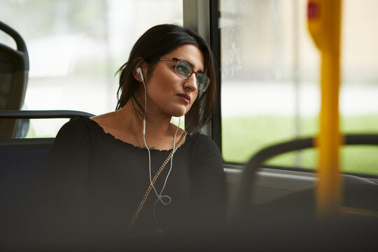 Young woman in bus looking through window