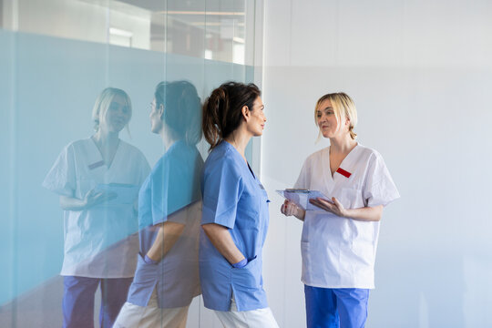 Female nurse and doctor talking in hospital