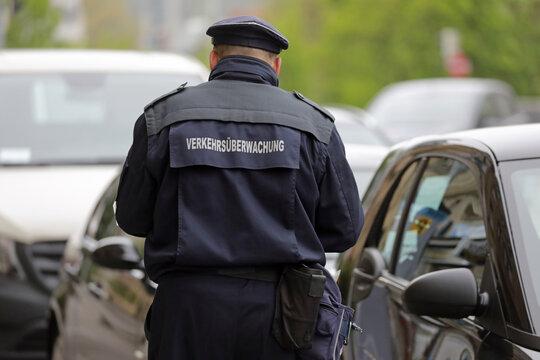 mann der verkehrsüberwachung in der stadt kontrolliert parkende autos