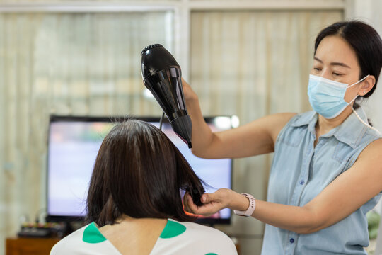 Woman wearing medical mask drying short hair with blow dryer.
