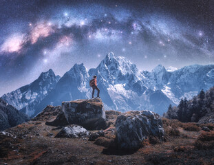 Fototapeta Arched Milky Way and sporty woman on the stone and mountains in snow at night. Girl with backpack, sky with bright stars, snowy rocks in Nepal. Space. Landscape with milky way arch. Travel and hiking